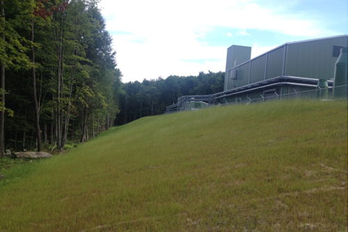 View north of Station's west-side embankment showing grass growth. Compressor Building is on the right.