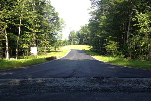 View west of Station entrance from Hungry Hill Road showing completed asphalt driveway and soil restoration on both sides.